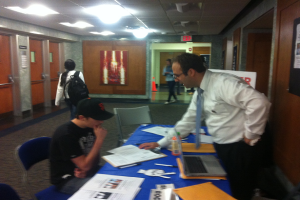 Dr. Klein explaining how to register to Mercy College Sophomore Rob Murphy.