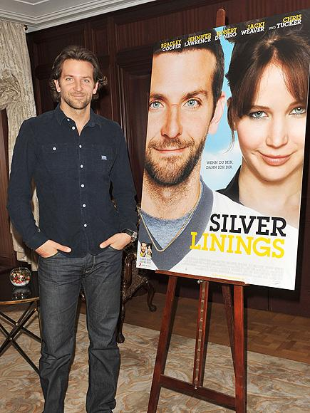 """BRADLEY COOPER LOOKING COOL STANDING NEXT TO THE MOVIE POSTER """"SILVER LININGS""""."""