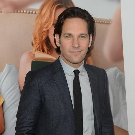 ACTOR PAUL RUDD WEARING A SUIT AND STANDING IN FRONT OF THE MOVIE POSTER FOR