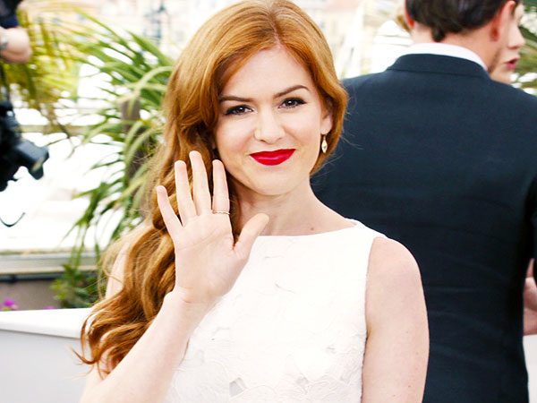 ACTRESS - ISLA FISHER WAVING HELLO AND WEARING BRIGHT RED LIPSTICK.