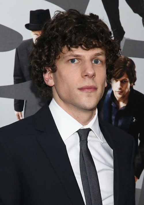 "ACTOR - JESSIE EISENBERG STANDING IN FRONT OF THE ""NOW YOU SEE ME"" MOVIE POSTER."