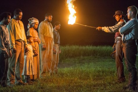 Cato-Alano-Miller-holding-a-fire-torch-confronting-some-of-the-Macon-7-slaves-800x533