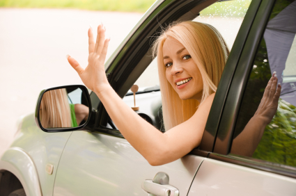 Driver-woman of car waves back as sign of farewell.