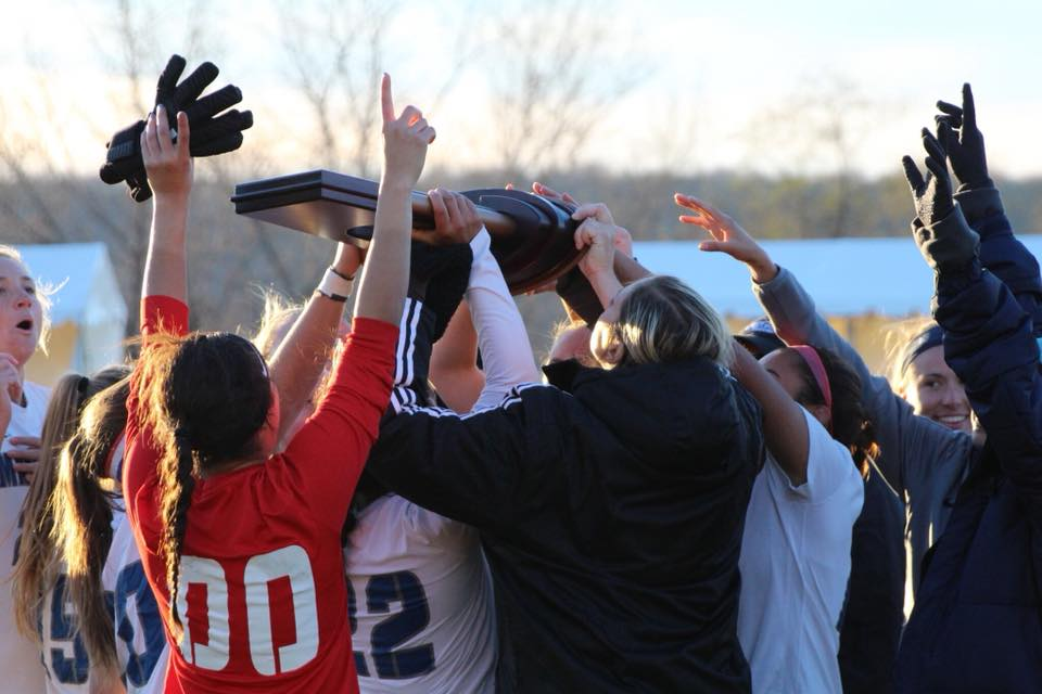 The Mercy Mavericks raise the Eastern Region Championship trophy in the air after a 2-0 win of LIU Post University.