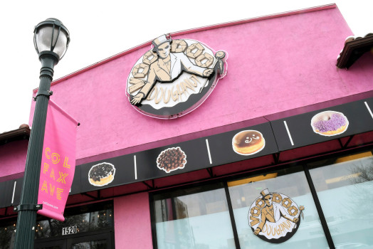 The company sign hangs over the windows of the storefront of Voodoo Doughnuts on East Colfax Avenue in Denver on Tuesday, April 4, 2017. A man trying to eat a half-pound glazed doughnut in 80 seconds as part of the shop's eating challenge choked to death Sunday at the business. (AP Photo/Thomas Peipert)