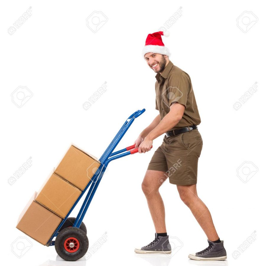 Happy delivery man in santa claus hat pushing a delivery cart and looking at camera. Full length studio shot isolated on white.