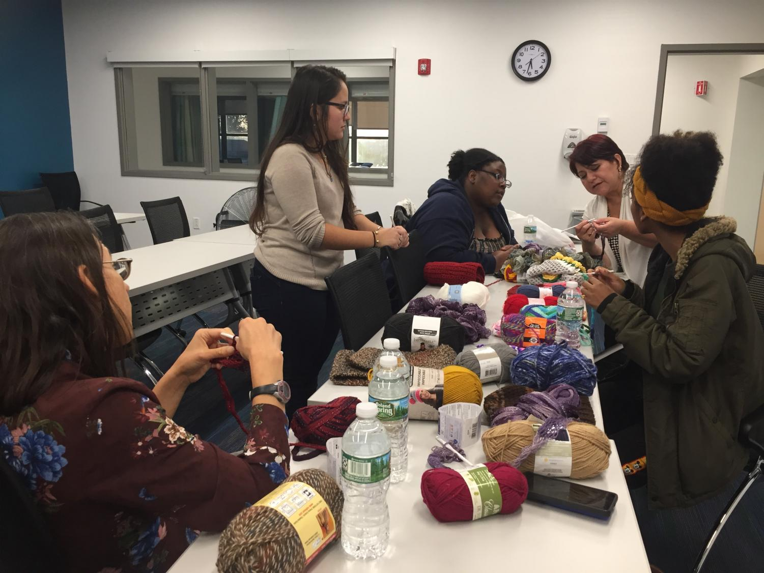 Mercy students and volunteers learn how to knit with the help of The Madristia Project founder Susana Luna and her daughter, Christal Luna.